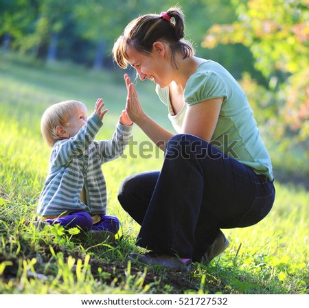 Happy mother play with her baby outdoor