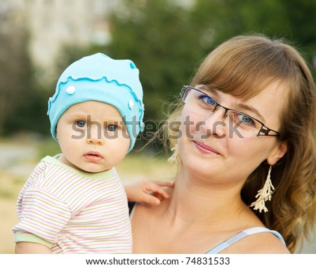 Happy mother playing with baby outdoor in summer - stock photo