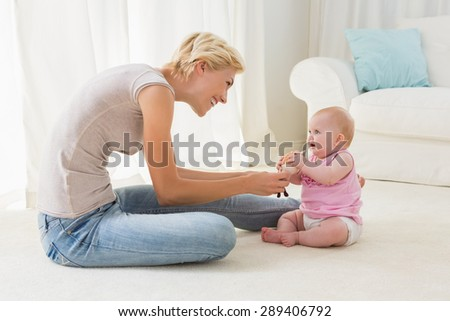 Happy mother playing with her baby girl at home in the living room - stock photo