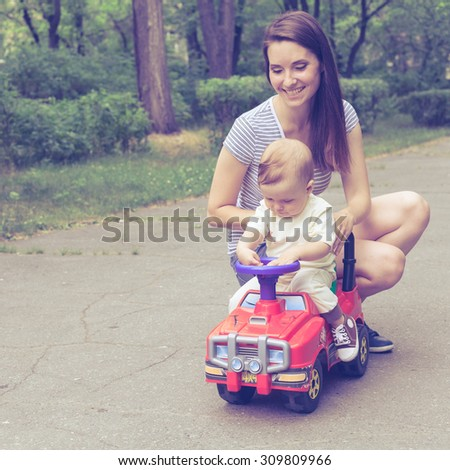 Happy mother playing with her baby in the park  at the day time - stock photo