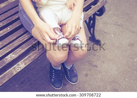 Happy mother playing with her baby in the park on the bench at the day time - stock photo