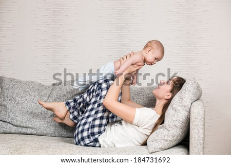 Happy mother playing with her cute loving baby at home - stock photo