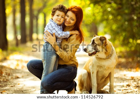 happy mother playing with her son in the park and dog sitting and watching - stock photo