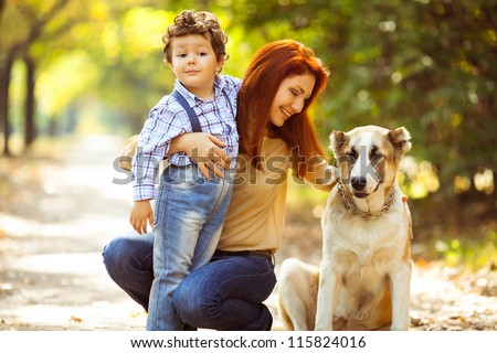 happy mother playing with her son in the park playing with the dog - stock photo