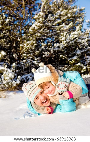 Happy mother playing with kid in snow - stock photo
