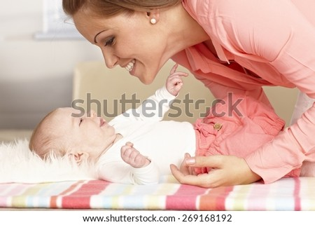 Happy mother playing with lying baby girl, smiling, talking. - stock photo