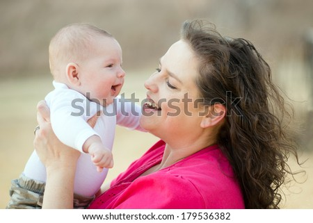 Happy mother playing with smiling, happy baby son - stock photo