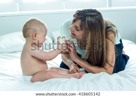 Happy mother playing with son on bed at home - stock photo