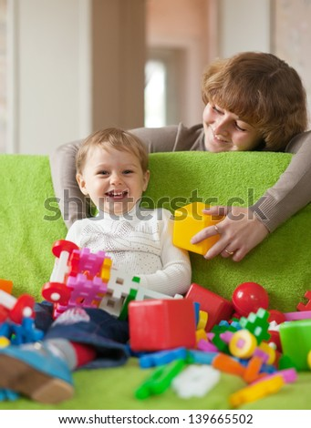 Happy mother plays with child in home interior