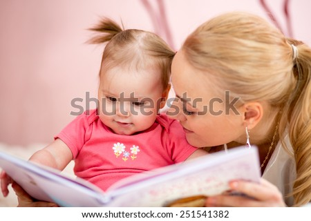 happy mother read a book to baby girl indoors - stock photo
