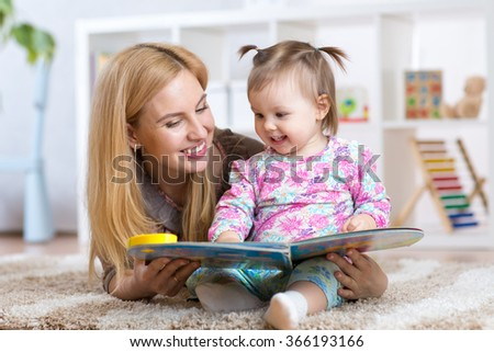 happy mother read a book to child girl indoors - stock photo