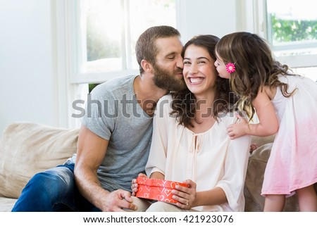 Happy mother receiving a gift from her husband and daughter in living room - stock photo