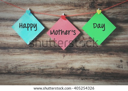 Happy mother's day on colorful paper with clothespin hanging on a string with wooden background, retro style. - stock photo