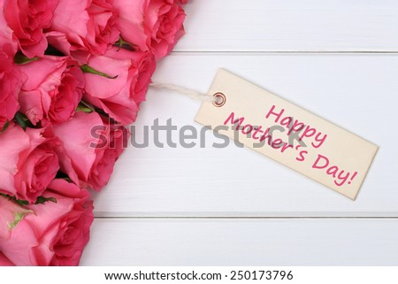 Happy mother's day with roses flowers on a white wooden board - stock photo