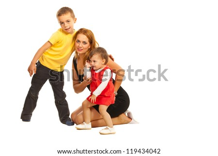 Happy mother sitting on floor and embracing her son and daughter isolated on white background - stock photo