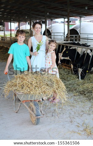 Happy mother, son and daughter stand near barrow at cow farm. - stock photo