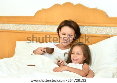 Happy mother spending time with little daughter in bed