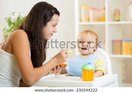 Happy mother spoon feeding her baby child - stock photo