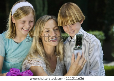 Happy mother taking self photo with teenage kids at birthday - stock photo