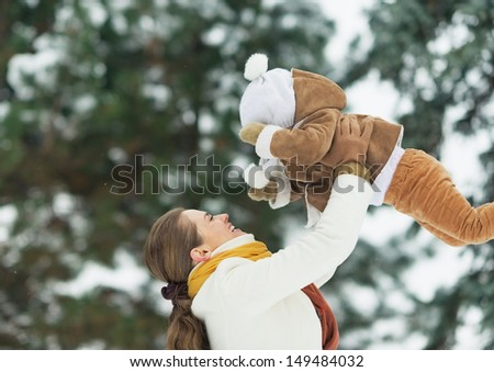 Happy mother throwing baby up in winter park - stock photo