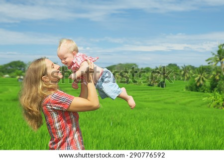 Happy mother tossing up joyful baby boy on Balinese green rice terraces background. Outdoors healthy child activity, active lifestyle on family summer vacation with son on Indonesian tropical island - stock photo