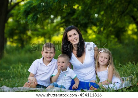 Happy mother, two sons and daughter dressed in white shirts are sitting on the grass in the park