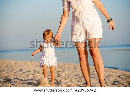 Happy mother walking with her little daughter on the beach in summer. They come together and hold hands. - stock photo