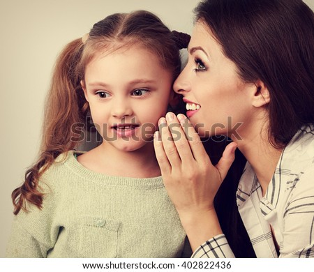 Happy mother whispering the secret to her cute kid girl in ear with fun face. Vintage close portrait - stock photo