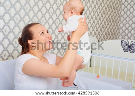 Happy mother with a baby in her arms. Up. - stock photo