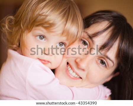 Happy mother with a child - shallow DOF, focus on woman's eyes
