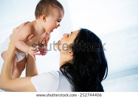 Happy mother with adorable baby - stock photo