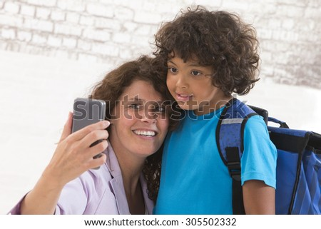 happy mother with adorable boy picturing themselves before first day of school - stock photo
