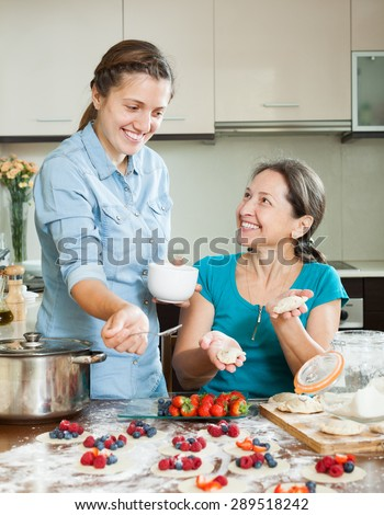 Happy mother with adult daughter  making berries dumplings at home kitchen - stock photo