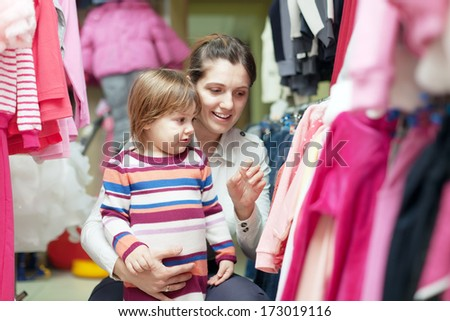 Happy mother with baby chooses wear  at clothes store - stock photo
