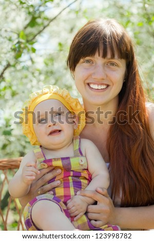 Happy mother with baby daughter  in spring garden