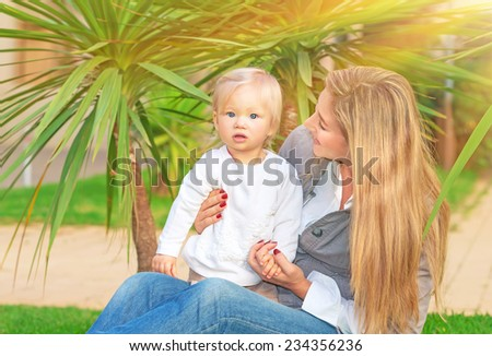 Happy mother with baby girl sitting on green field in tropical park in bright sunny day, enjoying motherhood, love and happiness concept - stock photo
