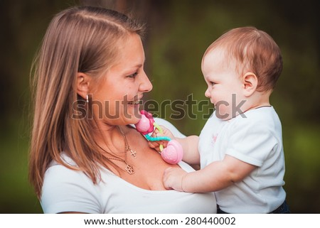 Happy mother with baby in summer green park - stock photo