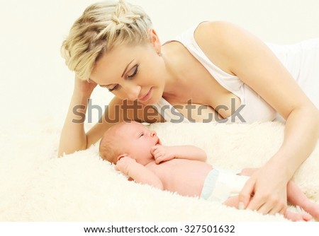 Happy mother with baby lying on bed together at home