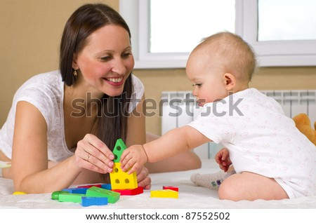 happy mother with baby playing toys - stock photo