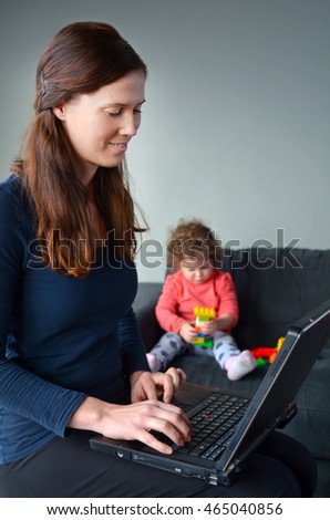 Happy mother with baby toddler works works on laptop. Woman works from home concept. copy space (BW)