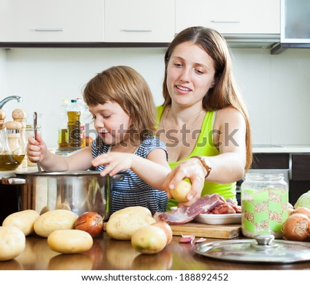 Happy mother with child cooking with meat and vegetables - stock photo
