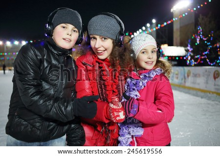 Happy mother with children make excellent gesture on the silent disco skating  - stock photo