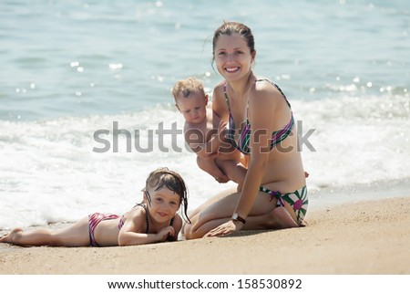 Happy mother with children on sand beach