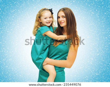 Happy mother with daughter in dress against the snowflakes - stock photo