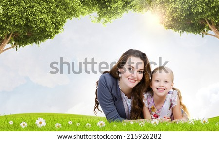 Happy mother with daughter sitting on green grass - stock photo