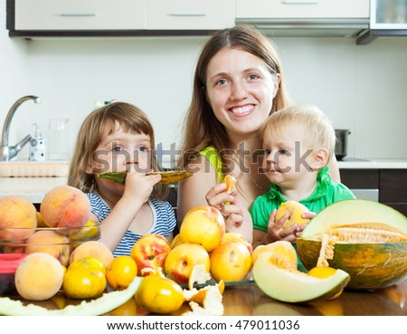 Happy mother with daughters eating melon and peaches over table
