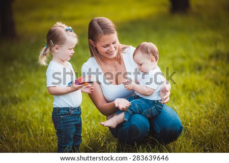 Happy mother with daughters relaxing in grass summer  park - stock photo