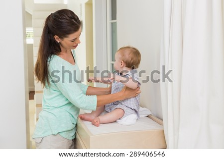 Happy mother with her baby boy at home - stock photo
