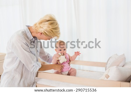 Happy mother with her baby girl at home in bedroom - stock photo