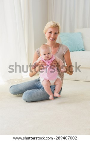 Happy mother with her baby girl at home in the living room - stock photo